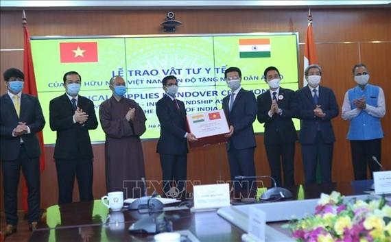 Bộ trưởng Bộ Thông tin và Truyền thông Nguyễn Mạnh Hùng, Chủ tịch Hội Hữu Việt Nam - Ấn Độ trao vật tư y tế cho Đại sứ Ấn Độ tại Việt Nam Pranay Verma. Ảnh:TTXVN