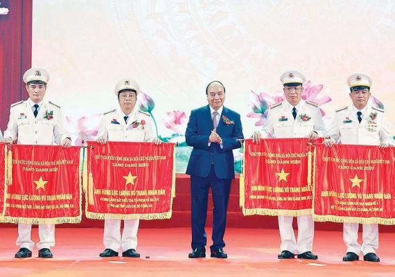 Thủ tướng Nguyễn  Xuân Phúc, Chủ tịch Hội đồng Thi đua - Khen thưởng Trung ương, trao tặng danh hiệu Anh hùng Lực lượng vũ trang nhân dân thời kỳ đổi mới  cho các  tập thể thuộc  Bộ Công an. Ảnh:  QUANG PHÚC