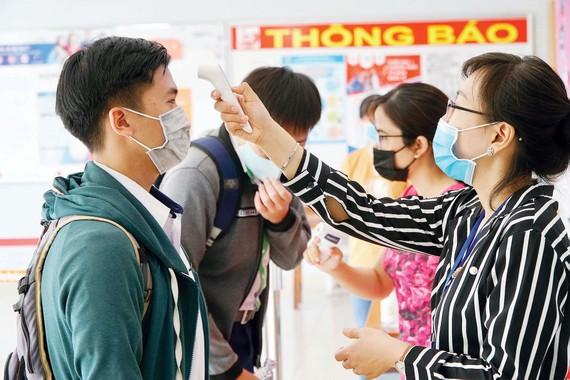 Đo thân nhiệt thí sinh tại điểm thi Trường THPT Gia Định, quận Bình Thạnh, TPHCM. Ảnh: QUANG PHÚC - HOÀNG HÙNG