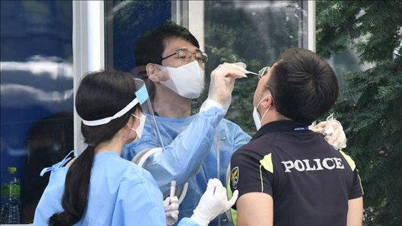 Nhân viên y tế lấy mẫu xét nghiệm COVID-19 cho một nhân viên an ninh tại Seoul, Hàn Quốc. Nguồn: TTXVN