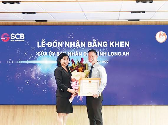 Ông Đinh Văn Thành, Chủ tịch HĐQT SCB nhận bằng khen từ bà Nguyễn Hồng Mai, Giám đốc Sở Lao động Thương binh và Xã hội tỉnh Long An
