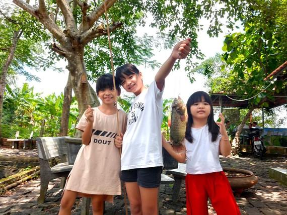 Trẻ em vui chơi ở quê bên vườn tược, cây trái. Ảnh: HOÀNG HÙNG