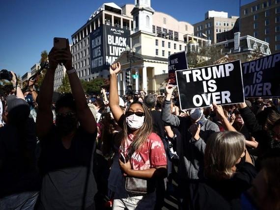 """Một số người mang theo cờ Mỹ bà biển hiệu: """"Trump đã kết thúc"""". Nguồn: REUTERS"""