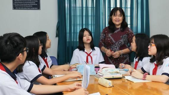 Cô Phùng Thị Ngọc Mai (Trường THCS Huỳnh Khương Ninh, quận 1, TPHCM) cùng học sinh trao đổi tại thư viện.Ảnh: HOÀNG HÙNG