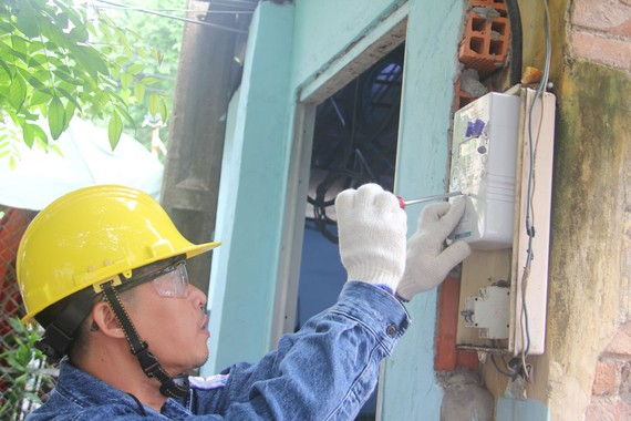 Nhân viên EVNHCMC gắn điện kế cho khách hàng