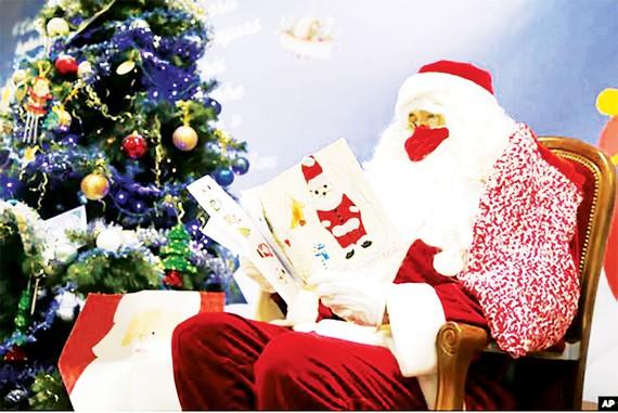 Một nhân viên bưu điện ở Libourne, Tây Nam nước Pháp  hóa trang thành ông già Noel đọc thư của các em bé
