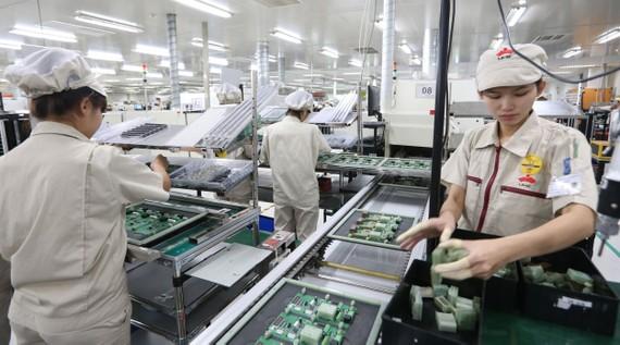 Việt Nam mở cửa nền kinh tế đã thu hút nhiều doanh nghiệp nước ngoài vào đầu tư, phát triển  (Trong ảnh: Sản xuất thiết bị điện tử tại Công ty UMC Việt Nam, Hải Dương).  Ảnh: QUANG PHÚC