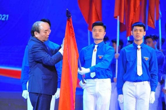 Thủ tướng Nguyễn Xuân Phúc gắn Huân chương Hồ Chí Minh  lên cờ truyền thống của Trung ương Đoàn TNCS Hồ Chí Minh. Ảnh: TTXVN