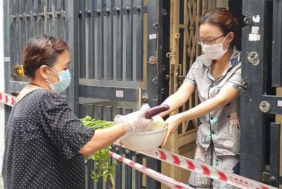 Người dân trong khu phong tỏa  tại quận Tân Phú (TPHCM)  được chăm lo thực phẩm,  an tâm ở nhà phòng chống dịch. Ảnh: THÁI PHƯƠNG