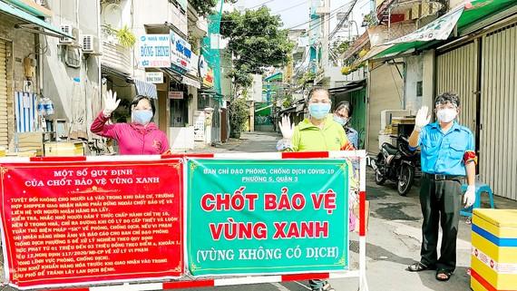 """Nhân dân tự nguyện tham gia trực chốt tự quản bảo vệ  """"vùng xanh"""" ở quận 3. Ảnh: VĂN MINH"""
