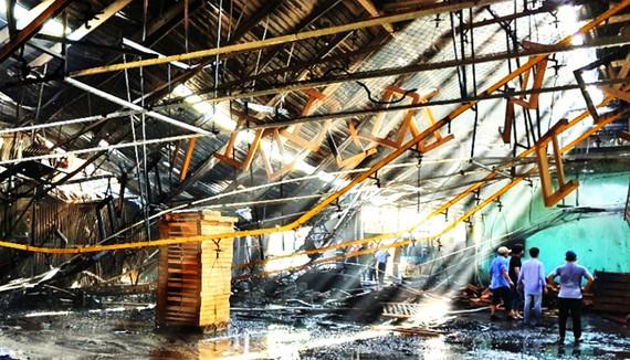 Lực lượng chức năng, công nhân nỗ lực dập tắt đám cháy  kho nhà xưởng TP Quy Nhơn, Bình Định trong ngày 30-7. Ảnh: XUÂN HUYÊN