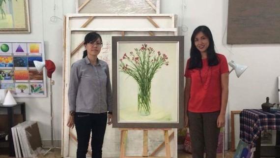 Họa sĩ Nguyễn Ngọc Đan (trái) bên bức tranh đấu giá