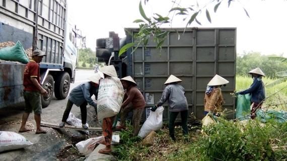 Người dân thu dọn dăm gỗ giúp tài xế vận chuyển sang xe trung chuyển. Ảnh:NGUYỄN TRANG