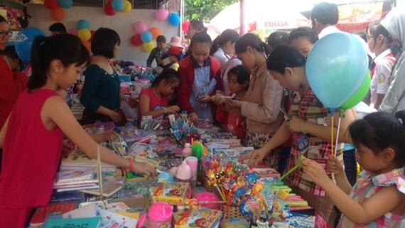 Phụ huynh và học sinh chọn mua các loại học cụ tại Ngày hội bán hàng bình ổn mùa khai trường 2017-2018 do UBND quận Gò Vấp tổ chức. Ảnh: UYỂN CHI