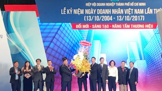 Phó Chủ tịch UBND TPHCM Trần Vĩnh Tuyến tặng lẵng hoa chúc mừng tới các doanh nhân