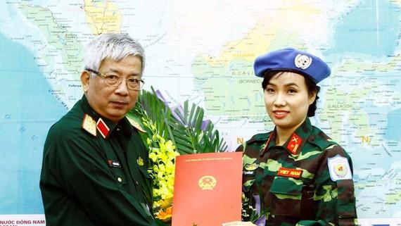 Thượng tướng Nguyễn Chí Vịnh trao Quyết định của Chủ tịch nước cho Thiếu tá Đỗ Thị Hằng Nga. Ảnh: TTXVN