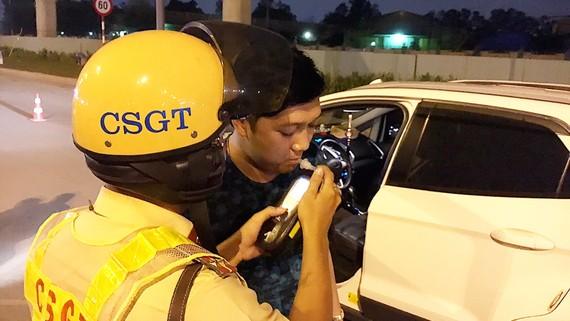 Cảnh sát giao thông đo nồng độ cồn để kiểm tra xử phạt những người điều khiển xe sau khi đã uống rượu bia. Ảnh: THANH HẢI