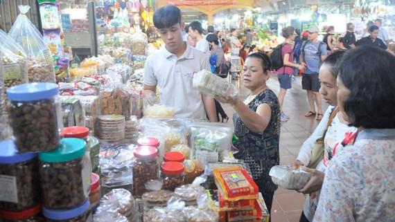 Người tiêu dùng chọn mua kẹo mứt tết tại chợ Bến Thành. Ảnh: CAO THĂNG