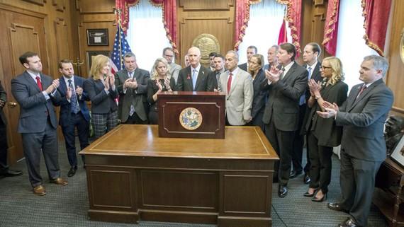 Thống đốc Rick Scott ký ban hành luật hạn chế súng tại Văn phòng Thống đốc ở Tallahassee, Florida, Mỹ, ngày 9-3-2018, dưới sự chứng kiến của các thành viên gia đình nạn nhân vụ xả súng trường học ở Parkland, Florida, Mỹ, ngày 14-2-2018. Ảnh: AP