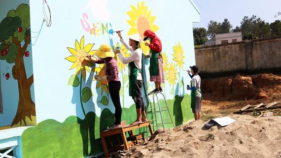 Các bạn trẻ cùng nhau vẽ trang trí những bức tường phòng học