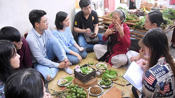 Các bạn trẻ lắng nghe chia sẻ về văn hóa trầu cau từ lớp người đi trước