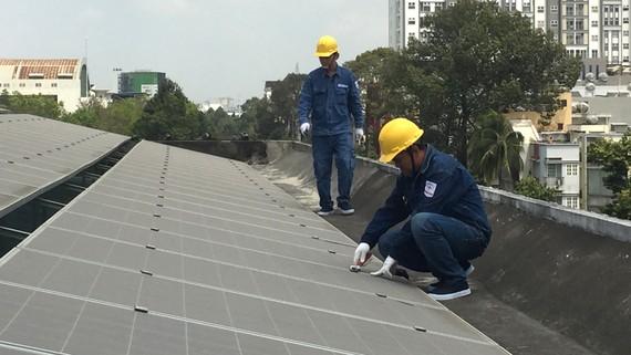 Nhân viên ngành điện lắp đặt điện mặt trời áp mái cho một đơn vị trên địa bàn TPHCM