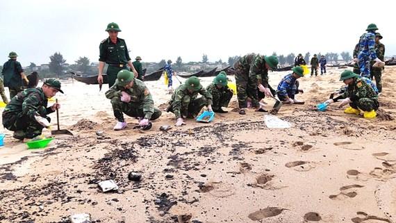Lực lượng chức năng thu gom cặn dầu loang trên bờ biển xã Kỳ Lợi, Hà Tĩnh