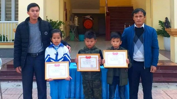 Lãnh đạo trường Tiều học Thạch Bình tặng giấy khen cho các em Đặng Khánh Ly, Nguyễn Quang Huy và Đặng Quốc Thiên