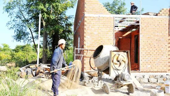 """Anh Trần Ngọc Tài (huyện Cư Mgar, tỉnh Đắk Lắk) bên căn nhà đang  được xây mới từ """"Quỹ tiết kiệm 1.000 đồng"""""""