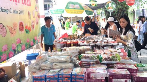 """Khách hàng chọn mua các loại bánh mứt và đặc sản của tỉnh Đồng Tháp  tại phiên chợ """"Tết xanh - quà Việt"""" tổ chức tại TPHCM từ ngày 17 đến 22-1"""