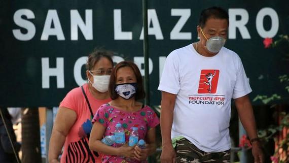 Người dân đeo khẩu trang đi ngang qua bệnh viện San Lazaro ở Manila, Philippines hôm 31-1-2020. Ảnh: The Philippines Star