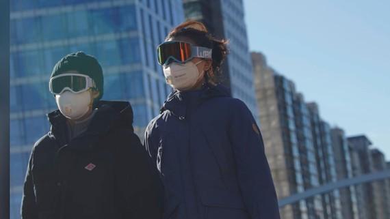 Người dân đeo kính và mặt nạ để tự bảo vệ mình tại Bắc Kinh, Trung Quốc hôm 16-2. Ảnh: REUTERS