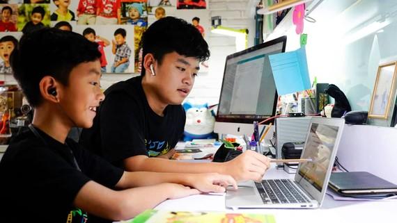 Em Nguyễn Huỳnh Thông, lớp 3 trường Võ Thị Sáu đang làm quen với cách học trực tuyến với sự hướng dẫn của người anh Nguyễn Huỳnh Bách, lớp 7 trường Đinh Thiện Lý. Ảnh: THANH TÙNG