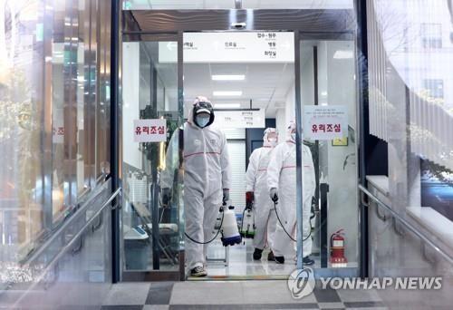 Lực lượng chức năng khử trùng một bệnh viện ở Busan, cách Seoul 450km về phía Đông Nam, ngày 24-2. Ảnh: Yonhap
