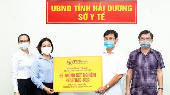Đại diện Tập đoàn T&T Group (bên trái) trao tặng hệ thống máy xét nghiệm Realtime – PCR cho đại diện Sở Y tế Hải Dương (bên phải)