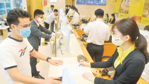 Hướng dẫn khách hàng giao dịch tại một ngân hàng. Ảnh: CAO THĂNG