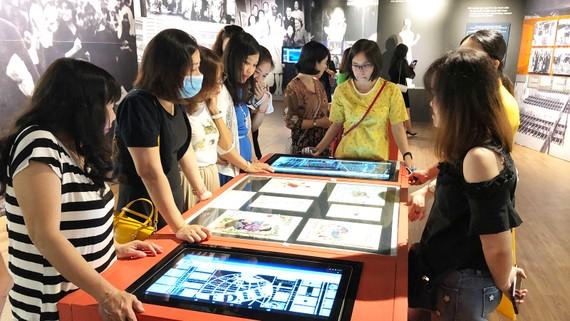 Khách tham quan tìm hiểu hiện vật trưng bày qua 2 màn hình kiốt thông tin hỗ trợ