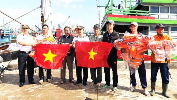 Vùng 4 Hải quân tặng cờ tổ quốc cho ngư dân Bình Định. Ảnh: NGỌC OAI