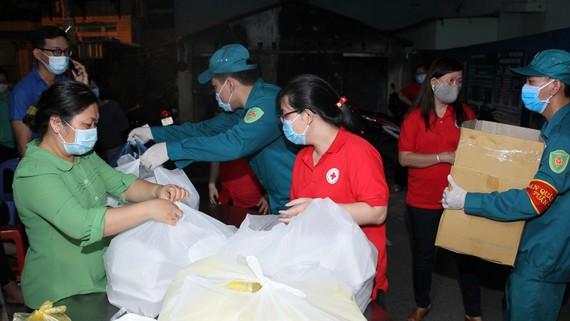 Các chiến sĩ dân phòng hỗ trợ tiếp tế cho bà con  đang cách ly tại khu Bình Tiên - Phạm Phú Thứ, quận 6. Ảnh: HOÀNG HÙNG