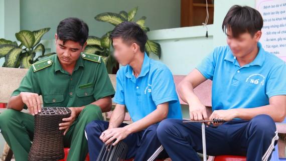 Anh Đinh Văn Tiến (trái) hướng dẫn học viên  trong một buổi lao động trị liệu