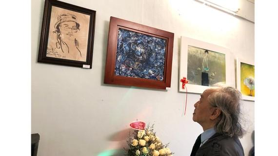 """Nhà văn, dịch giả Bửu Ý bên bức tranh chân dung họa sĩ Bửu Chỉ do nhạc sĩ Trịnh Công Sơn vẽ, được trưng bày tại triển lãm tranh """"Trịnh và những âm ba"""""""