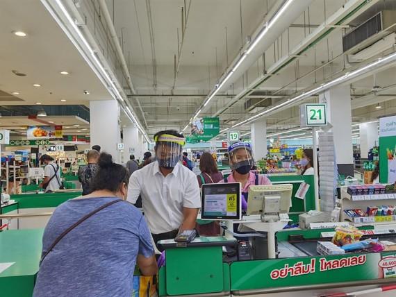 Nhân viên siêu thị tại Bangkok đeo khẩu trang và che mặt để phòng, ngừa Covid-19