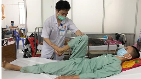 Anh Lục Rồi Hỷ (22 tuổi) được  kỹ thuật viên hỗ trợ tập vật lý  trị liệu, phục hồi  chức năng