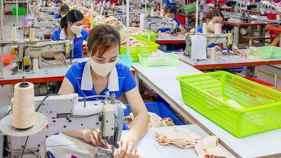 Giảm lãi suất cho vay, ưu tiên DN sản xuất. Trong ảnh: Công nhân sản xuất  tại Công ty Dệt may Kim Dung, quận 12, TPHCM. Ảnh:  HOÀNG HÙNG