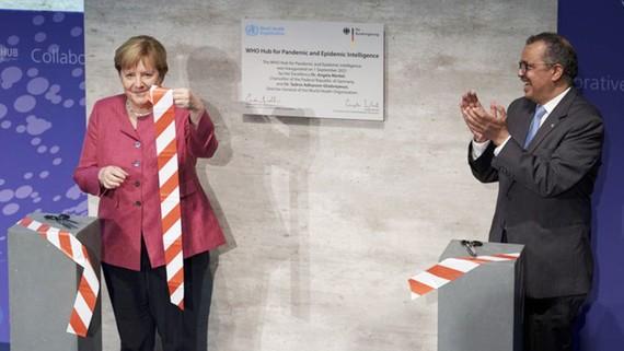 Tổng Giám đốc WHO Tedros Adhanom Ghebreyesus (phải) và Thủ tướng Đức Angela Merkel cắt băng khai trương Trung tâm cảnh báo sớm đại dịch tại thủ đô Berlin, Đức. Ảnh: AP
