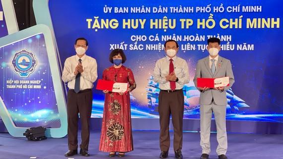 Bí thư Thành ủy TPHCM Nguyễn Văn Nên và Chủ tịch UBND TPHCM Phan Văn Mãi  tặng Huy hiệu TPHCM cho các doanh nhân tiêu biểu. Ảnh: HOÀNG HÙNG