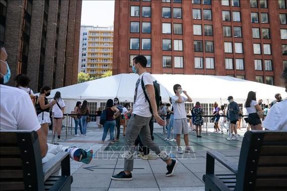 Sinh viên xếp hàng chờ xét nghiệm COVID-19 tại trường đại học New York, Mỹ. Ảnh: AFP/TTXVN
