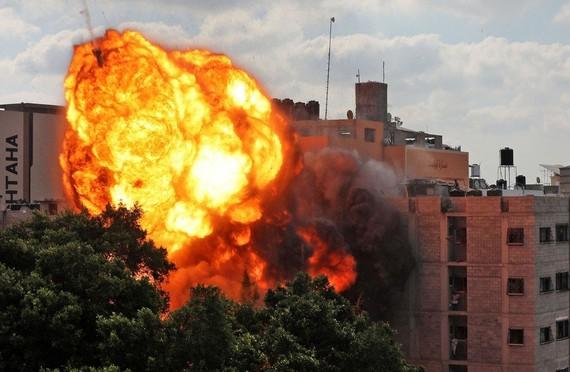 Một quả rocket do lực lượng Israel bắn nhấn chìm tòa nhà Al-Walid ở thành phố Gaza hôm 13/5. Trong bối cảnh xung đột Israel-Palestine bước sang tuần thứ 2, ĐHĐ LHQ sẽ họp công khai vào ngày 20/5, thỏa luận về tình hình tại đây. (Nguồn: Reuters)