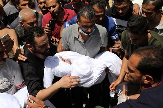 Một người Palestine ôm thi thể của một đứa trẻ bị giết trong cuộc không kích của Israel vào nhà của họ, trong lễ tang ở thành phố Gaza, ngày 16 tháng 5 năm 2021. [Ảnh / Tân Hoa xã]