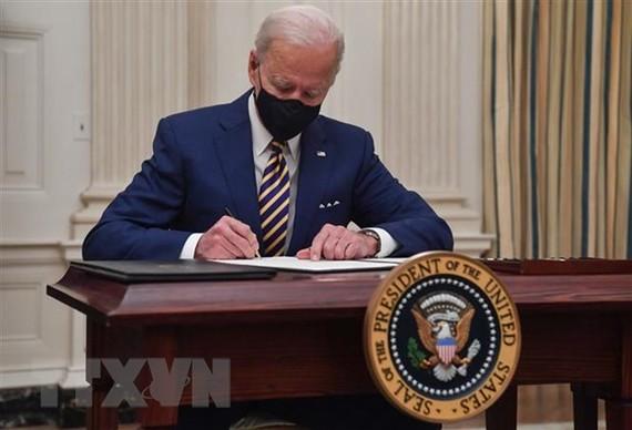 Tổng thống Mỹ Joe Biden ký sắc lệnh tại Nhà Trắng ở Washington DC. (Ảnh: AFP/TTXVN)